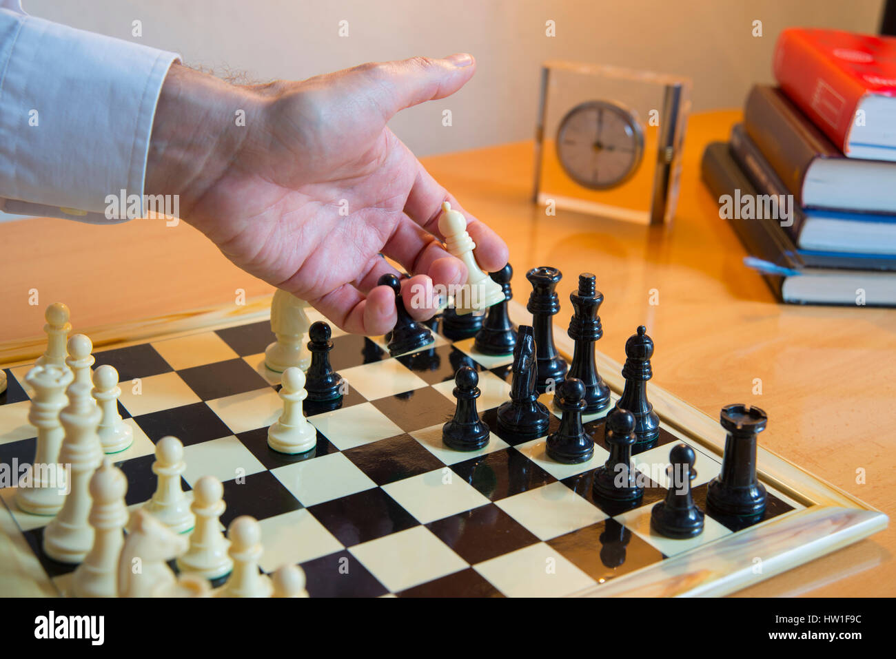 Man's hand playing chess. - Stock Image