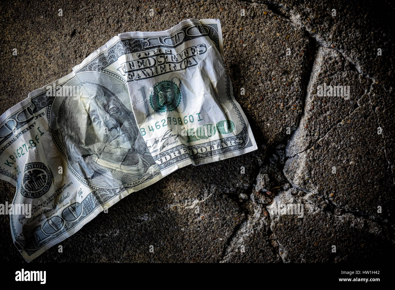 United States one hundred dollar bill on dirty ground - Stock Image