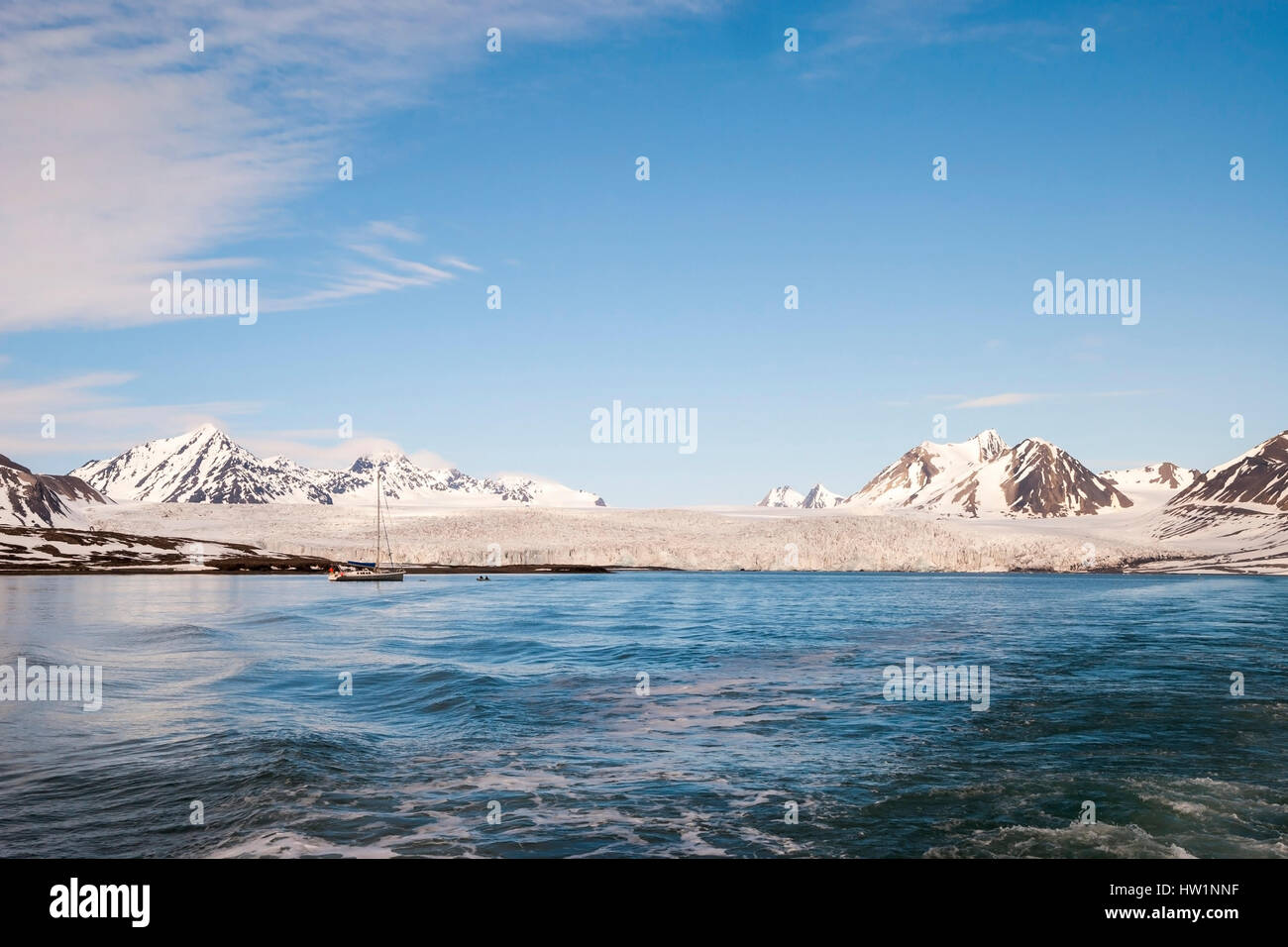 Sailing boat in front of the glacier and mountains in Svalbard, Arctic - Stock Image