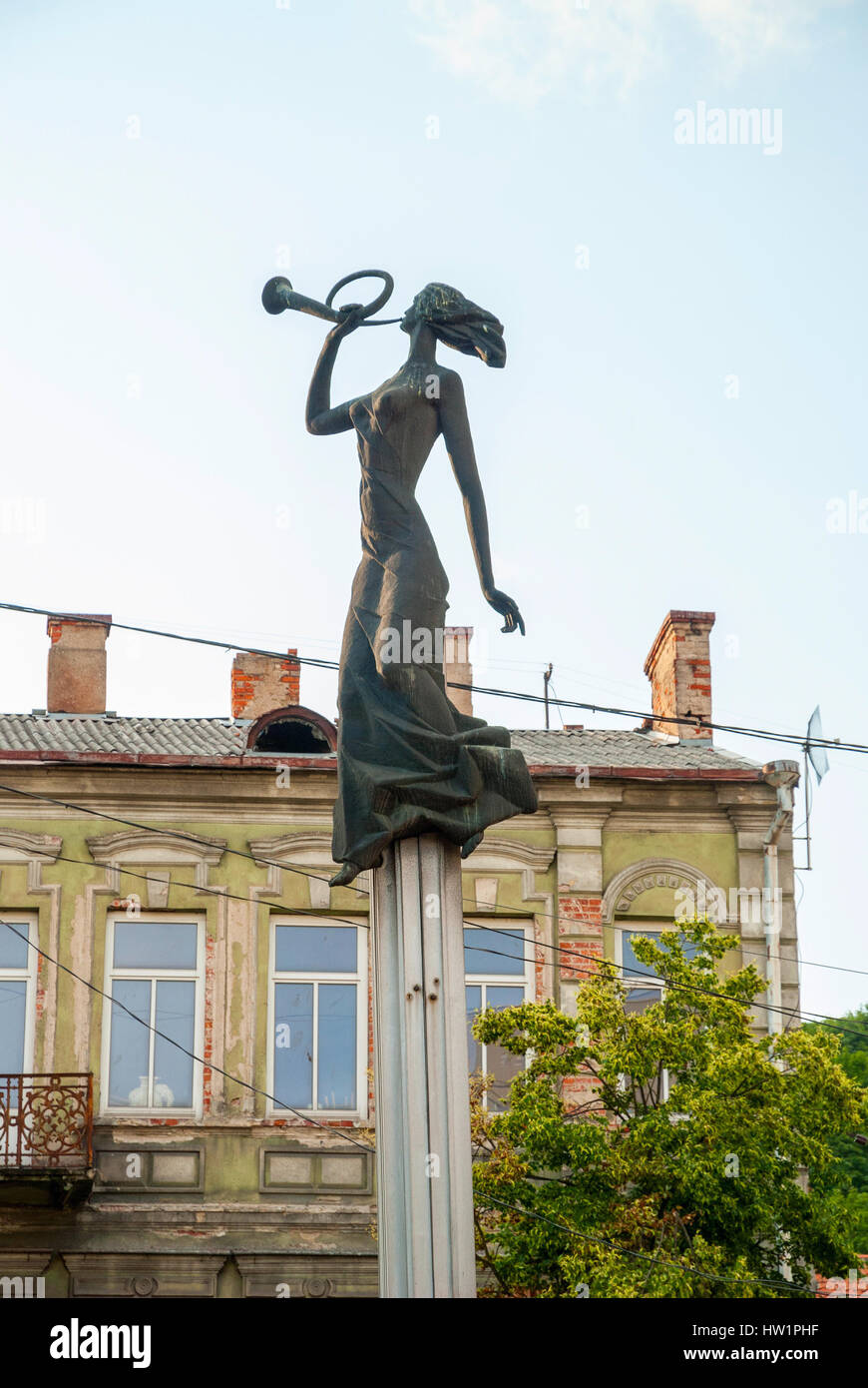 Close-up of stone statue of woman with horn on pillar in Kaunas, Lithuania - Stock Image