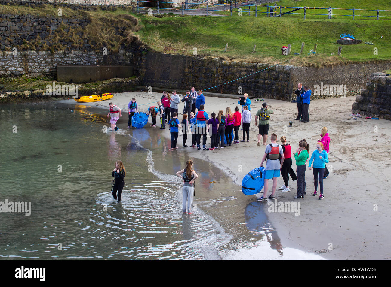 youth group takes advantage of a fine spring afternoon for water sports in the small harbor at Ballintoy on the - Stock Image
