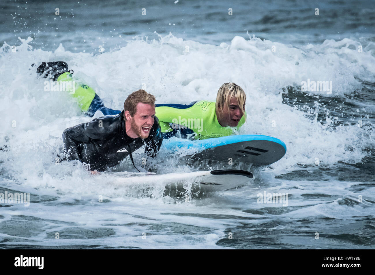 Two surfers in Klitmoller which is a popular surfing destination in Northern Denmark. Klitmoller is also known as - Stock Image