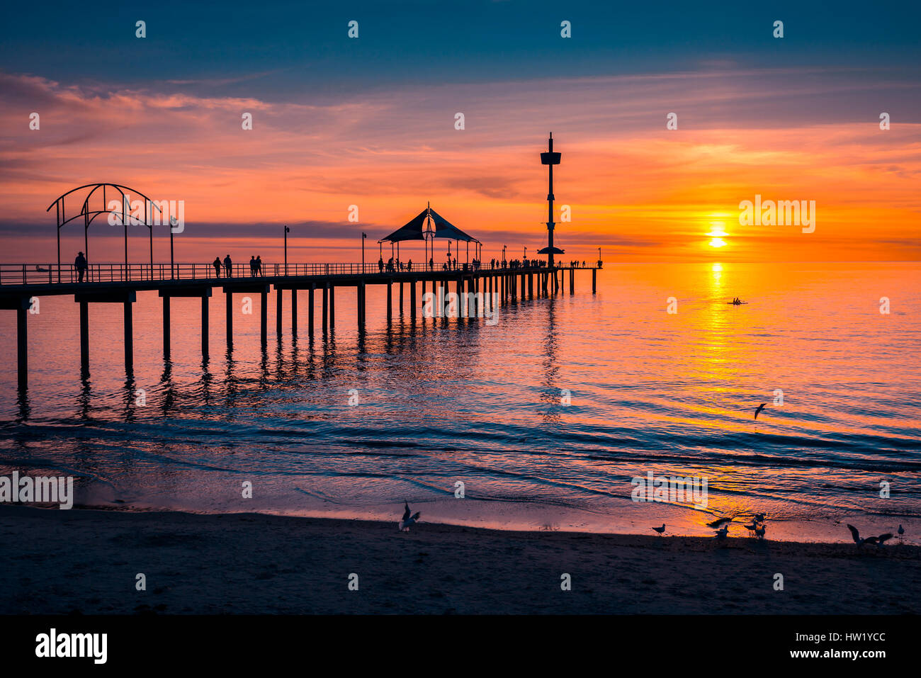 People walking on Brighton Jetty at sunset, South Australia - Stock Image