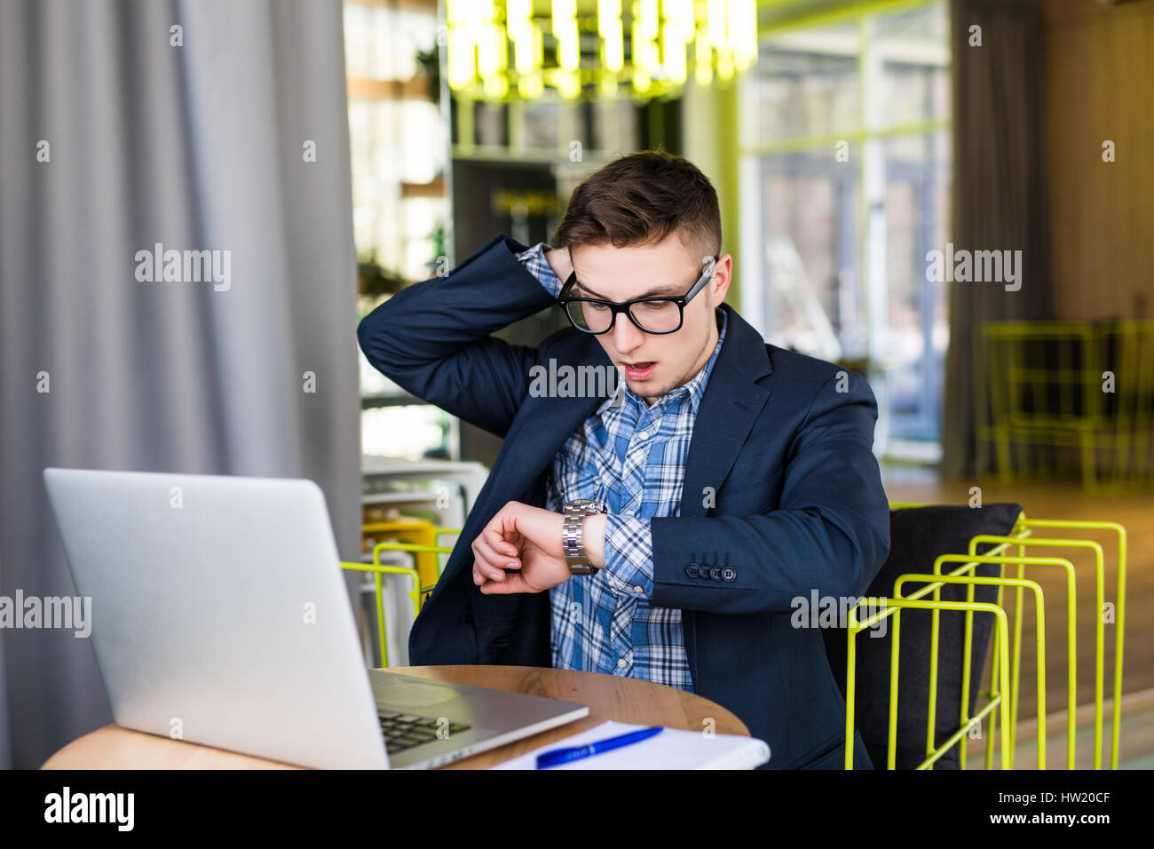 Worried businessman running out of time watching the clock at office - Stock Image