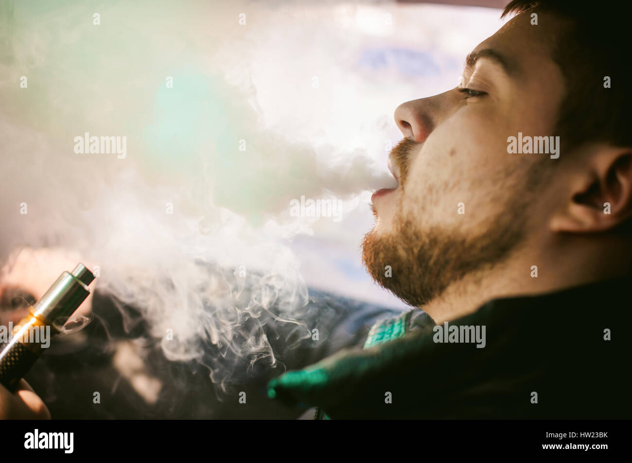 young vaper man with beard vaping mechanical mod. Guy smokes an electronic cigarette by blowing a smoke vapor - Stock Image