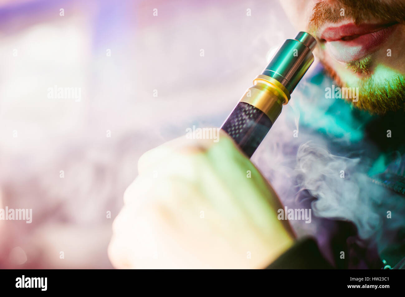 young vaper man with beard vaping mechanical mod. Guy smokes an electronic cigarette by blowing a smoke vapor. Bringing - Stock Image