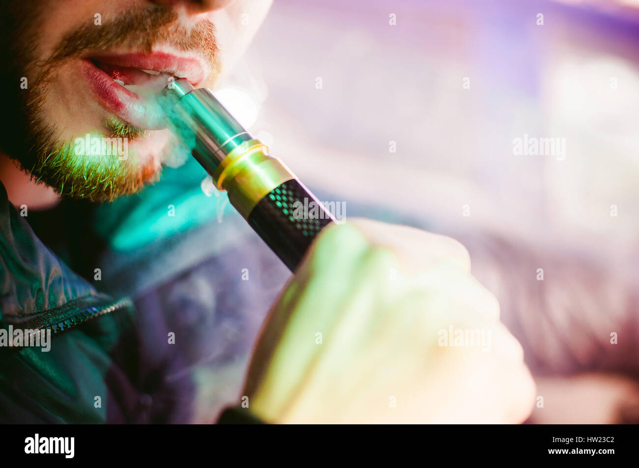 young vaper man with beard vaping mechanical mod. Guy smokes an electronic cigarette by blowing a smoke vapor. Bringing - Stock Image