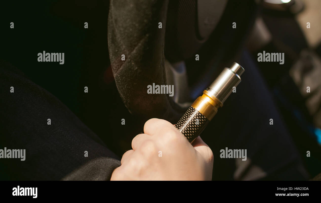 young vaper man with beard vaping mechanical mod. Guy smokes an electronic cigarette by blowing a smoke vapor. Holds - Stock Image