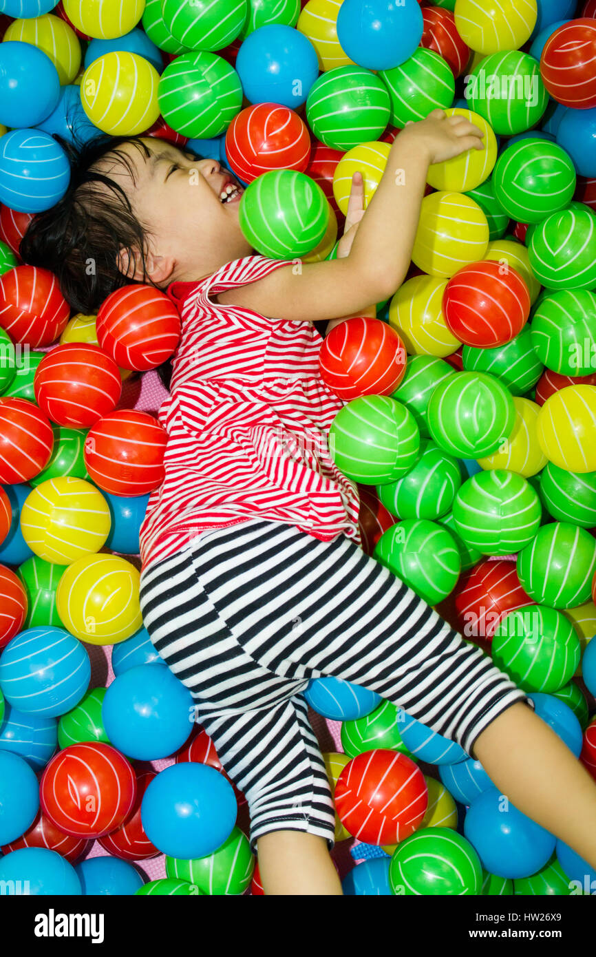 Asian Chinese girl hide in colorful ball pool at indoor playground. - Stock Image