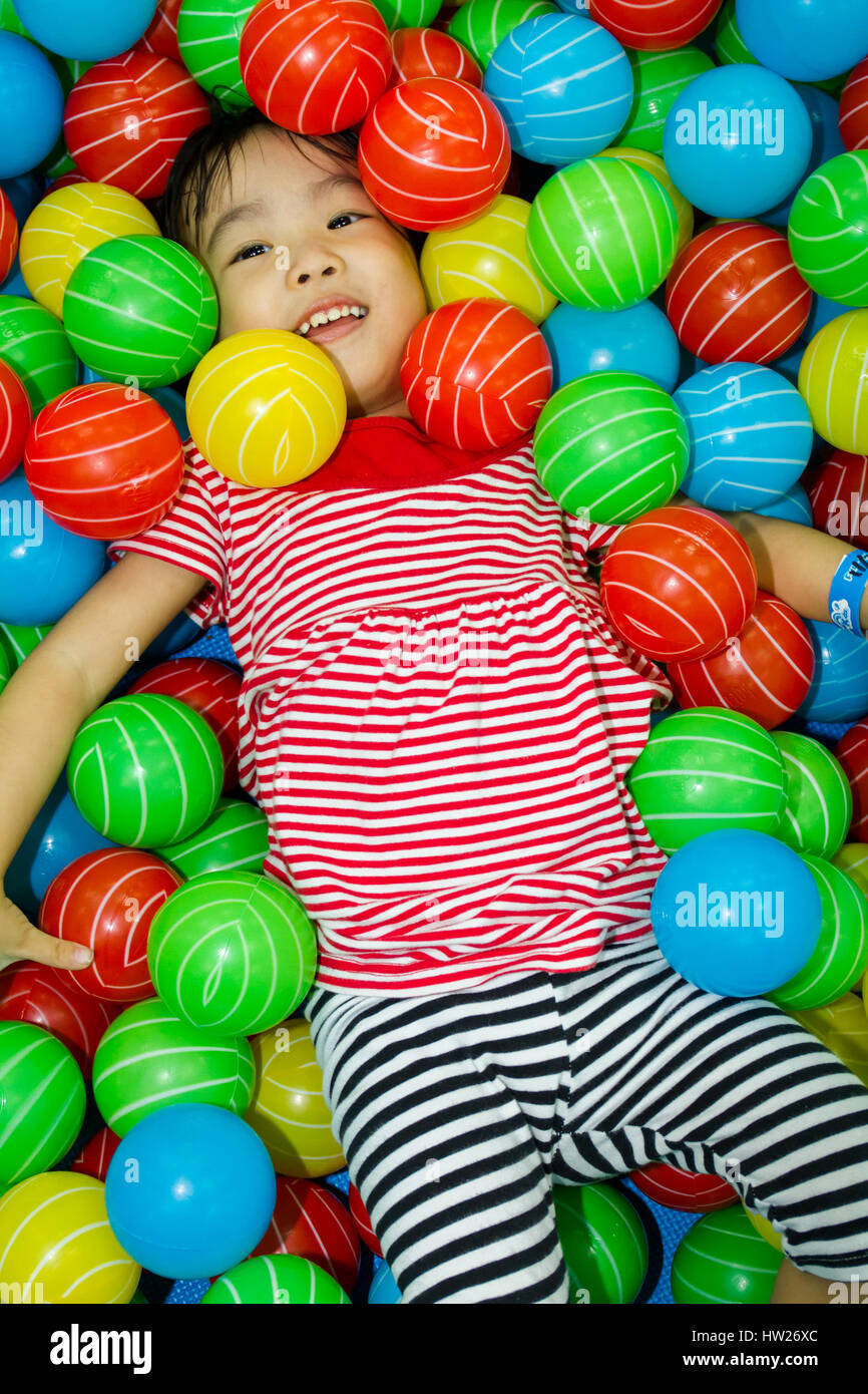 Asian Chinese girl hide in colorful ball pool at indoor playground. Stock Photo