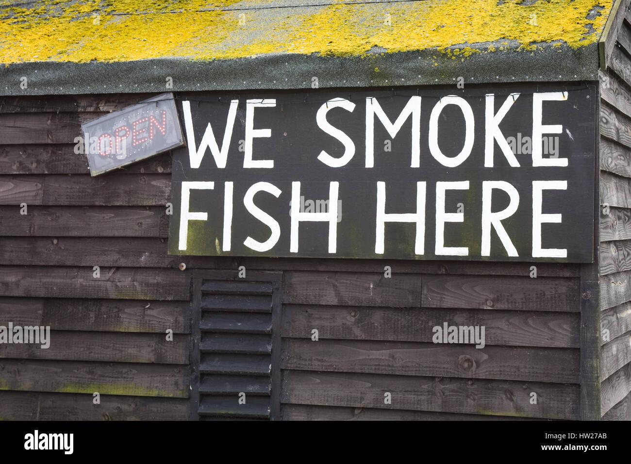 We smoke fish here amusing sign on an Aldeburgh fishing hut - Stock Image