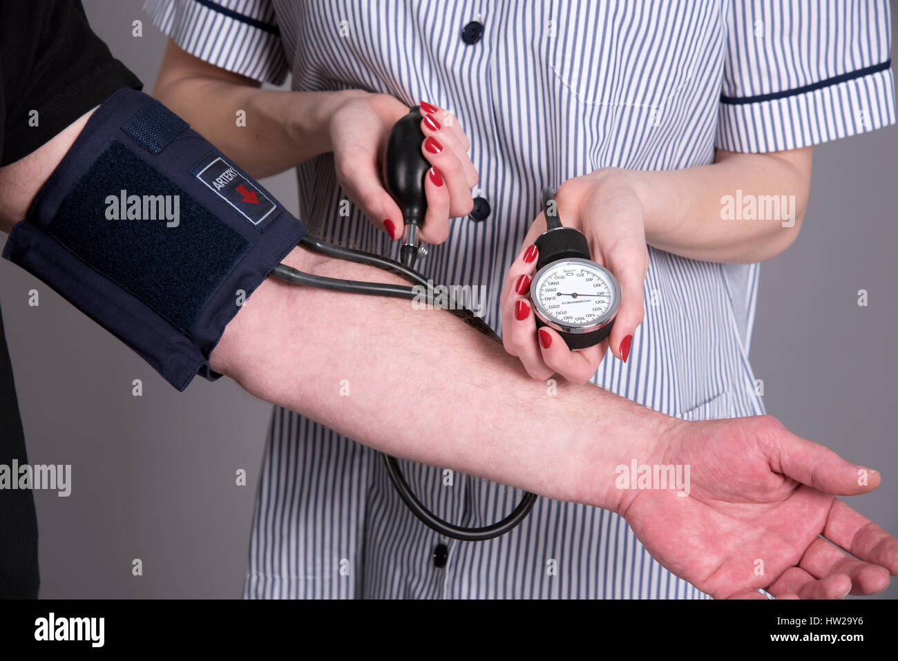 Nurse using a blood pressure monitor on a patient - Stock Image