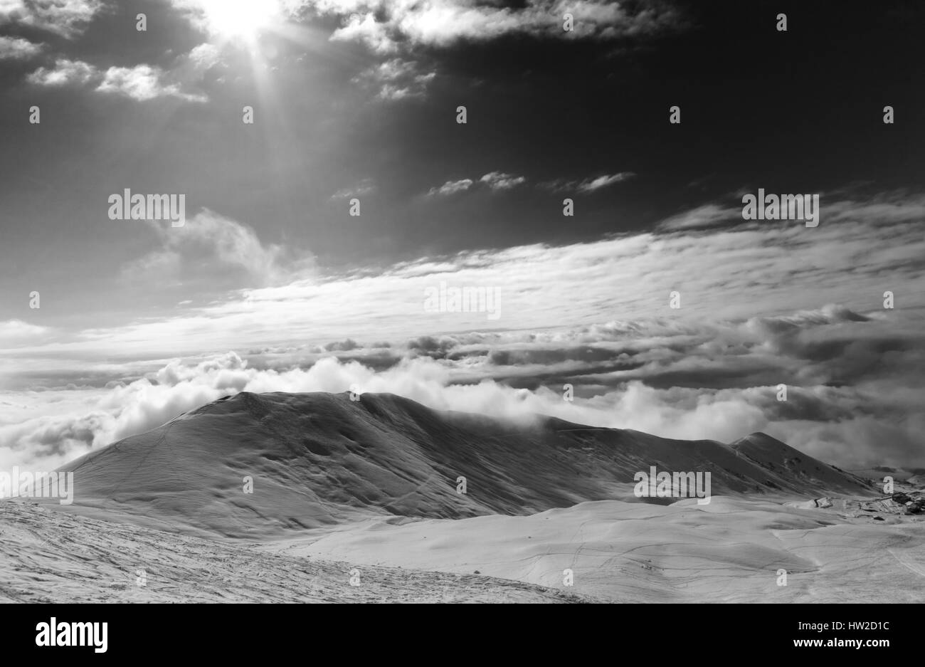 Black and white view on off-piste slope in clouds and sky with sun. Caucasus Mountains, Georgia, region Gudauri. - Stock Image