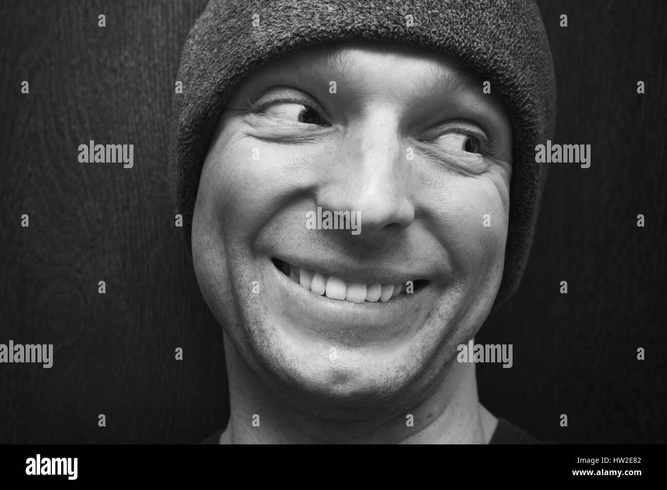 949383118ec Young handsome smiling man in gray hat. Close-up studio face portrait over  dark wooden wall background