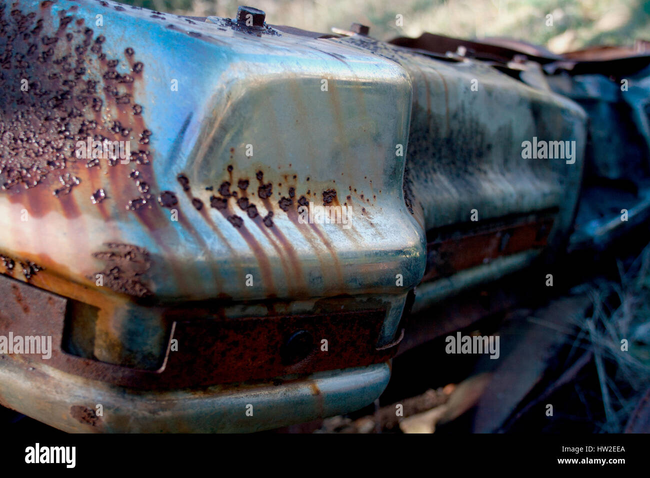 The rusted ruins of an old automobile left to rust. - Stock Image