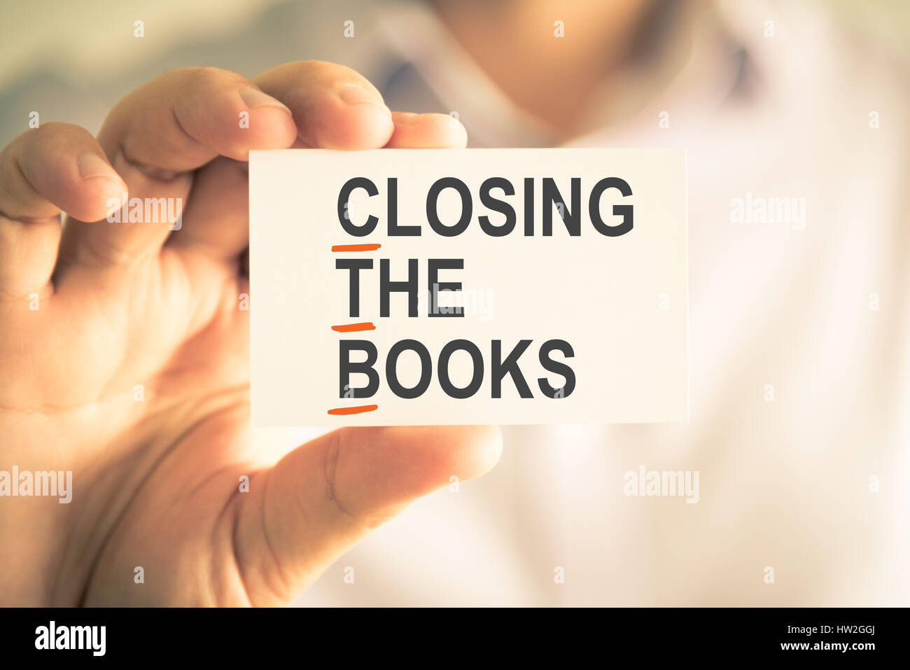 Closeup on businessman holding card with CTB CLOSING THE BOOKS Stock Photo  - Alamy