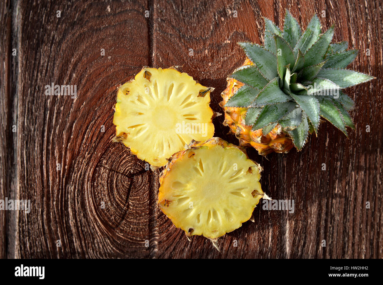 Fresh Asian small pineapple on wooden plate in outdoor hard sunlight and dark shadow - Stock Image