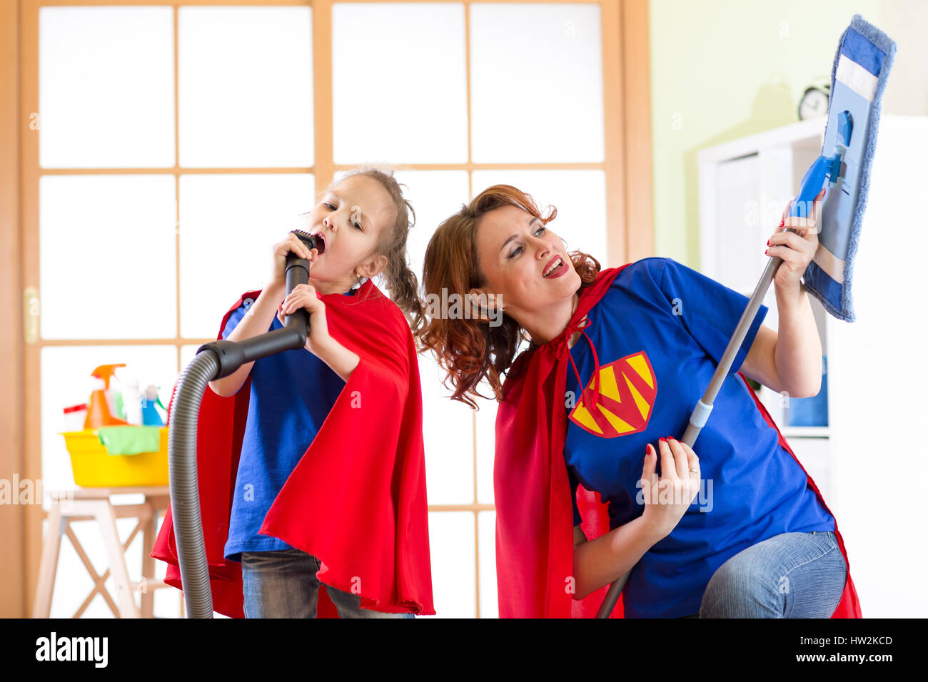 Preschooler girl and her mother dressed like superheroes. Middle-aged woman and kid playing while doing cleanup - Stock Image