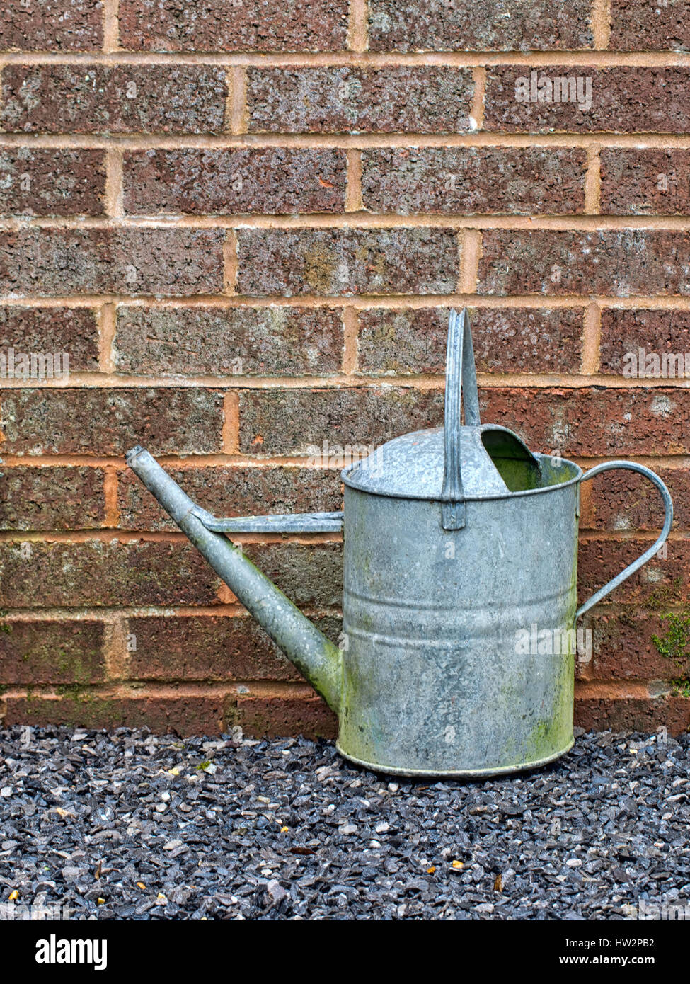 Galvanized old watering can. Old fashioned gardening equipment. - Stock Image