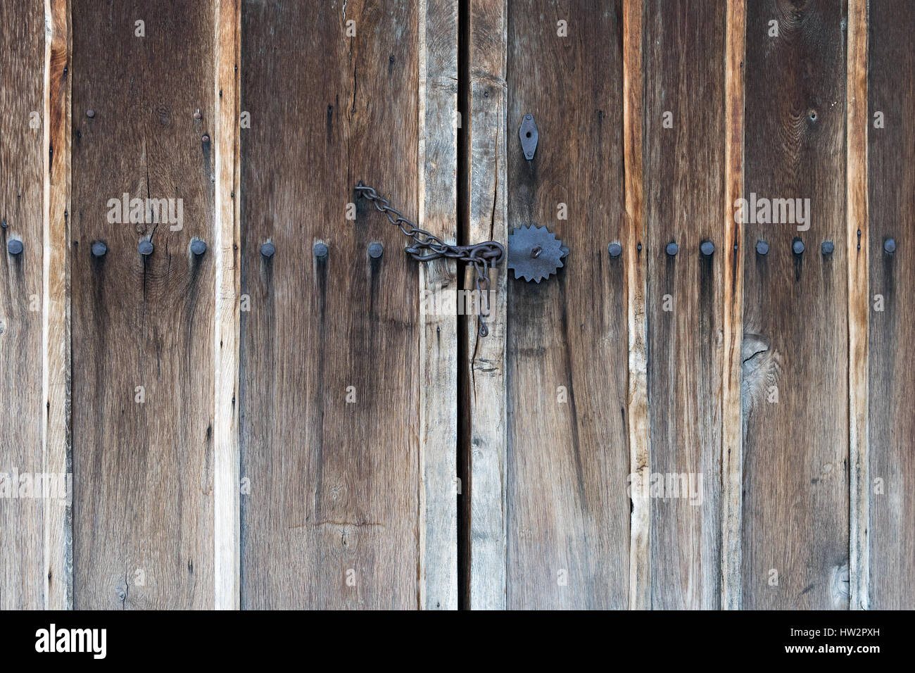Chain Locked Wooden Door With Big Iron Nails And Metal Ornaments