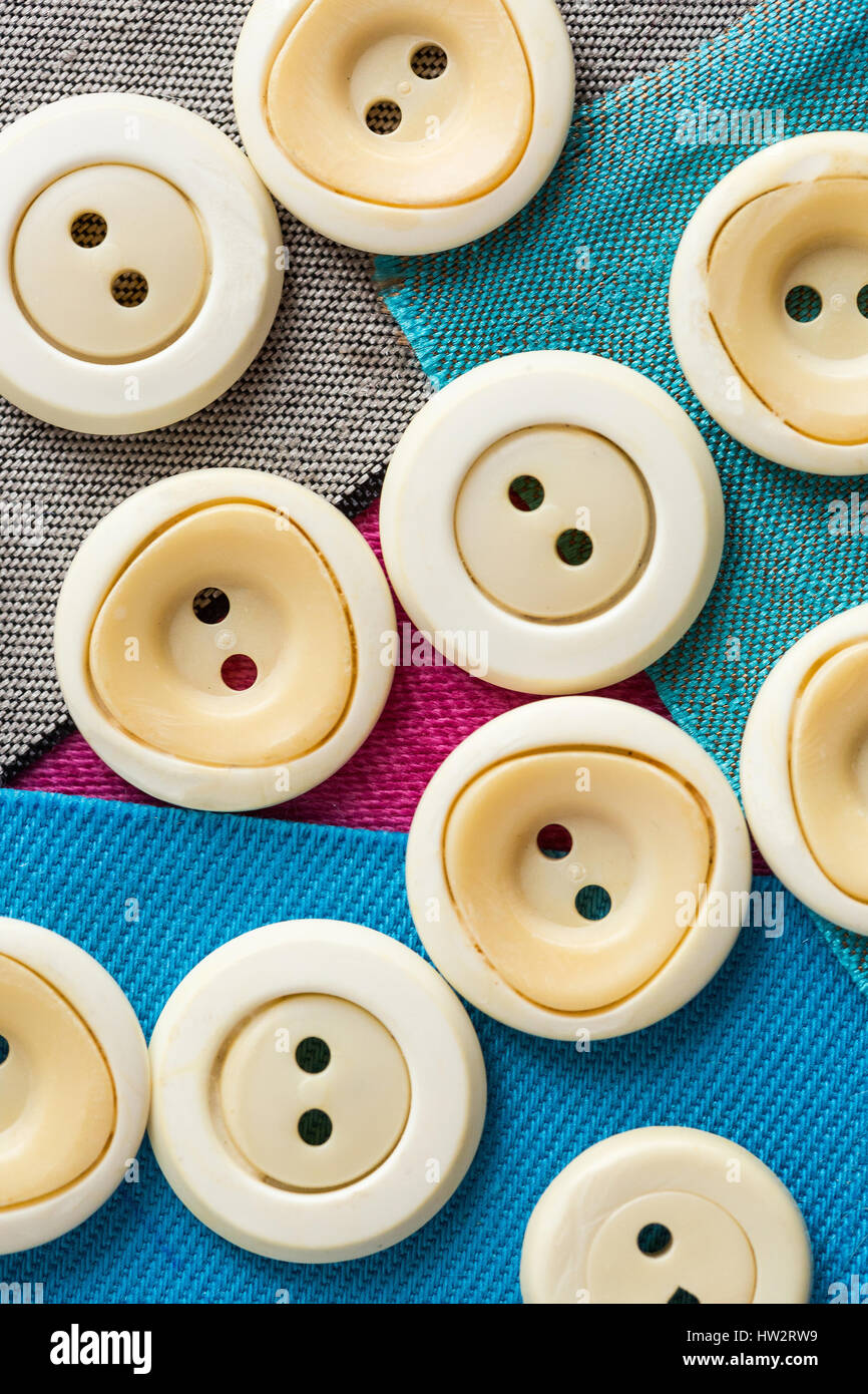 concept with beige monophonic buttons on pieces of colored fabric close up, macro, top view, flat lay. Stock Photo