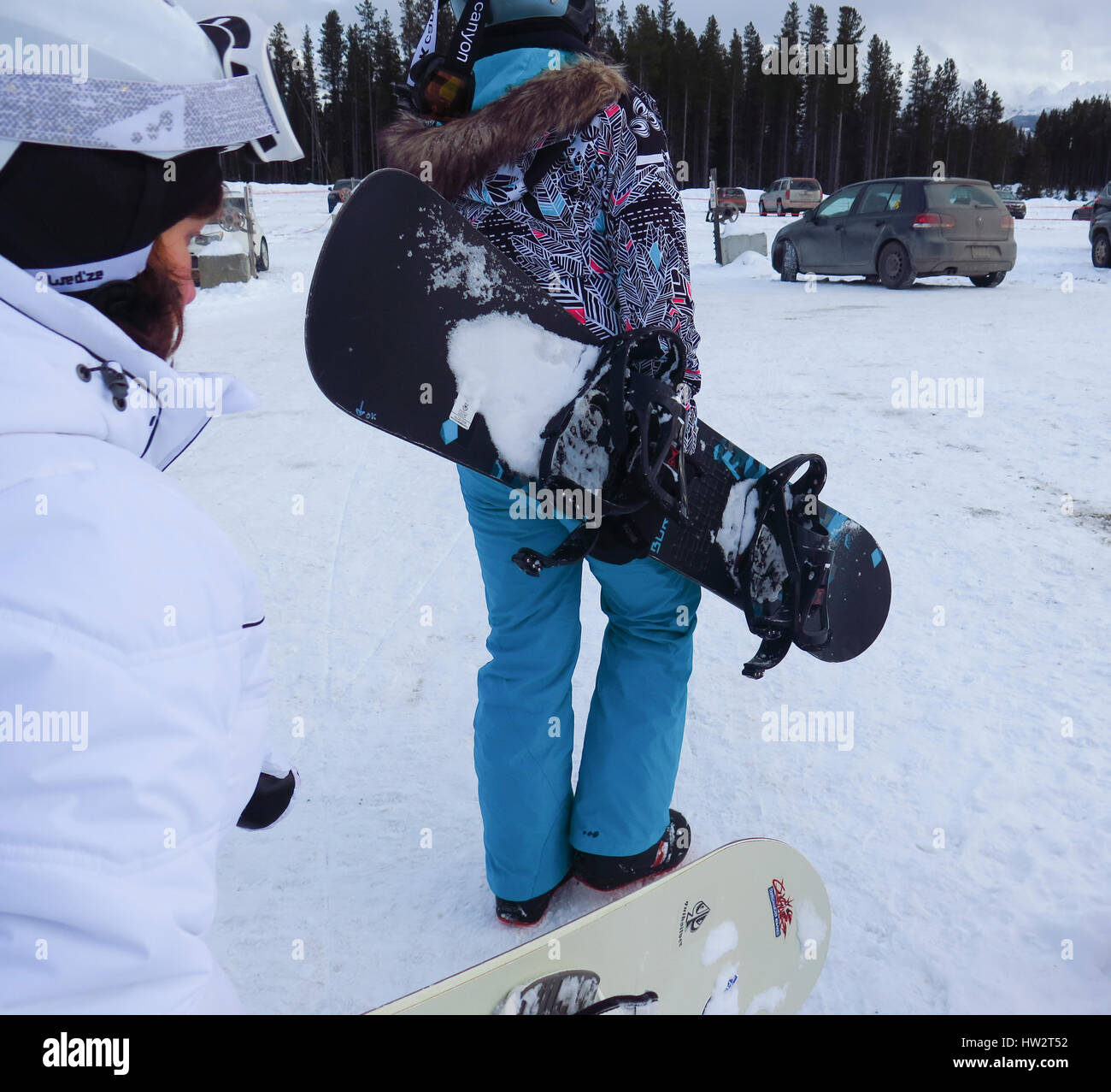 Young woman walking with snowboard - Stock Image