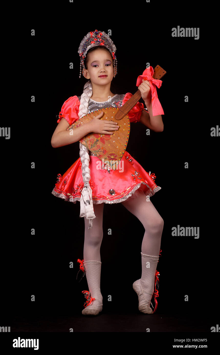 Cute little girl wearing native russian costume isolated on black background. She is dancing and holding balalaika - Stock Image