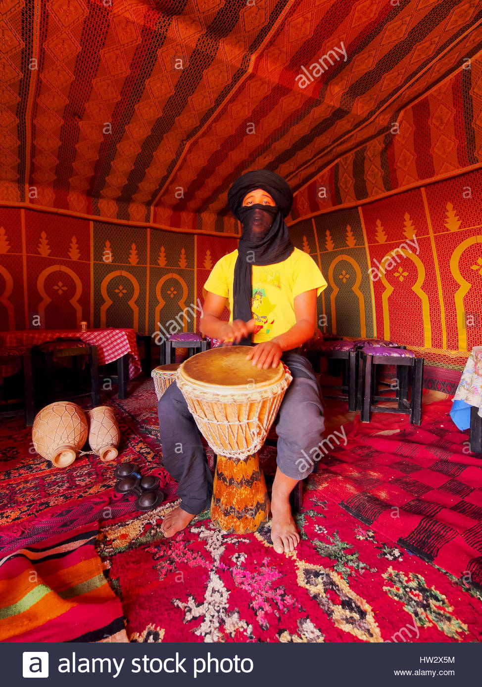 ZAGORA DESERT, MOROCCO, MAY 04: Unidentified Berber man playing the drum inside of the tent on the Zagora Desert - Stock Image