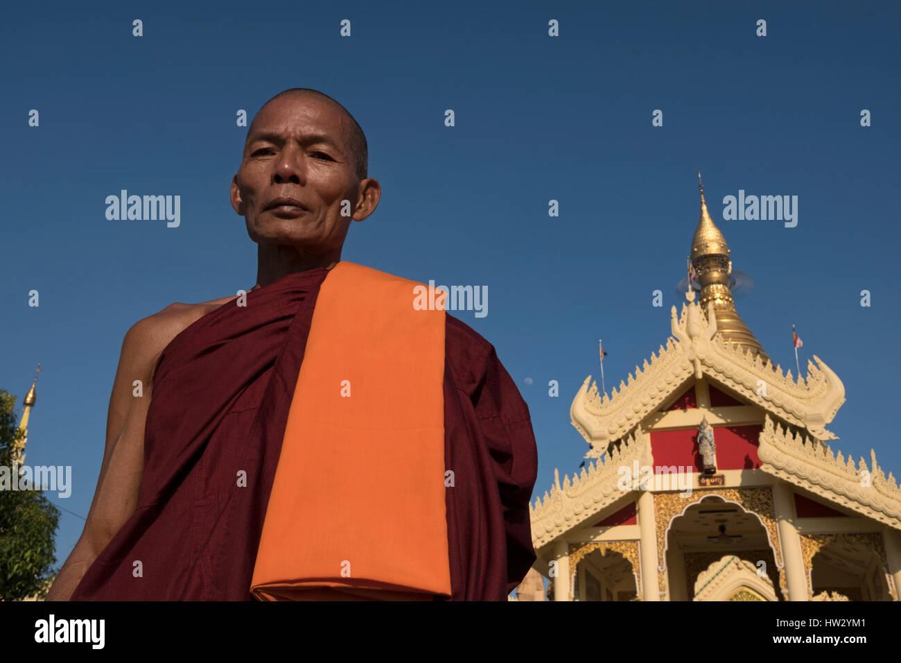 A Buddhist monk at the entrance of the Maha Wizaya Pagoda in Yangon, Yangon Region, Myanmar - Stock Image