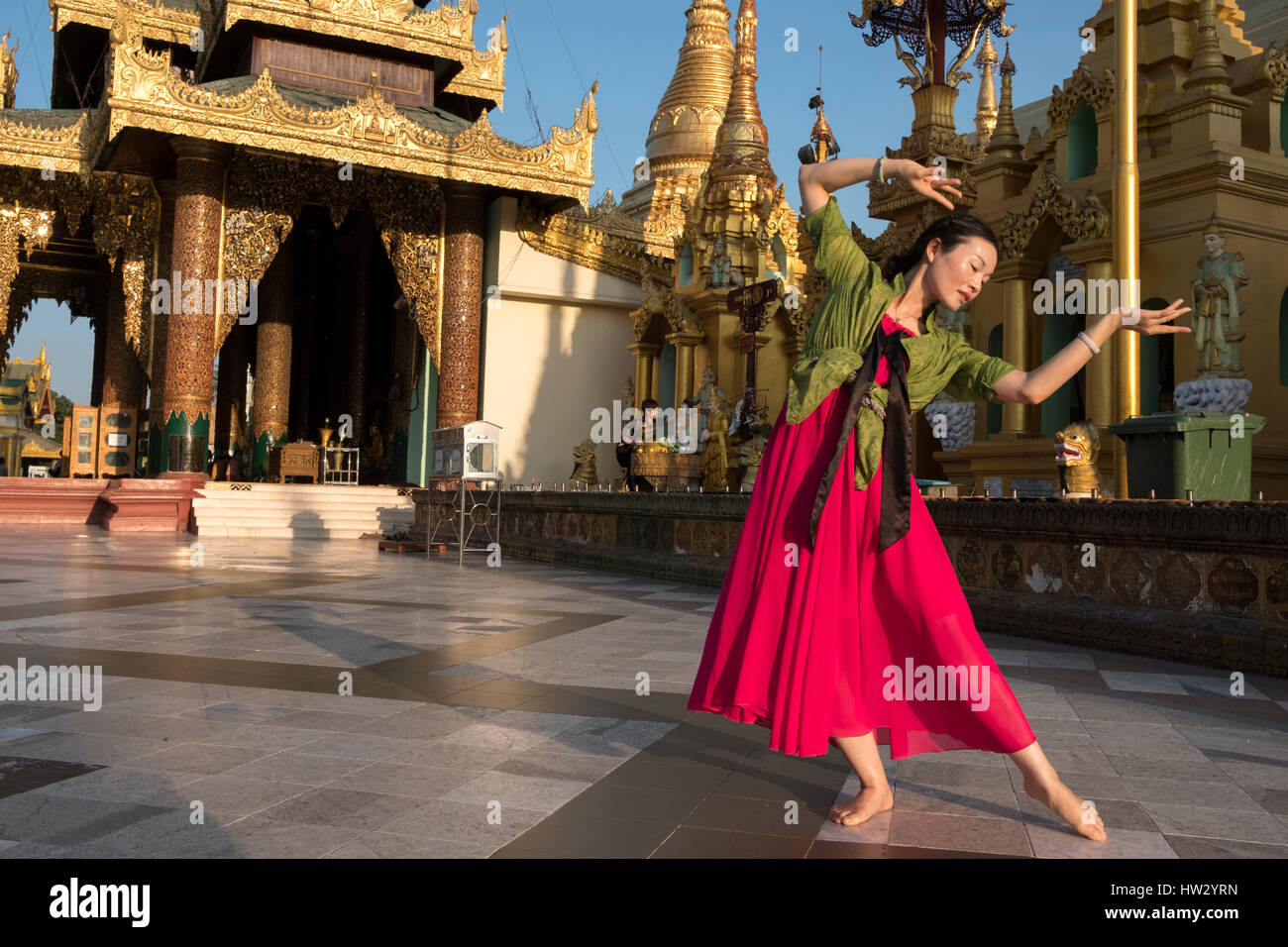 A woman dances at the Shwedagon Pagoda in Yangon, Yangon Region, Myanmar - Stock Image