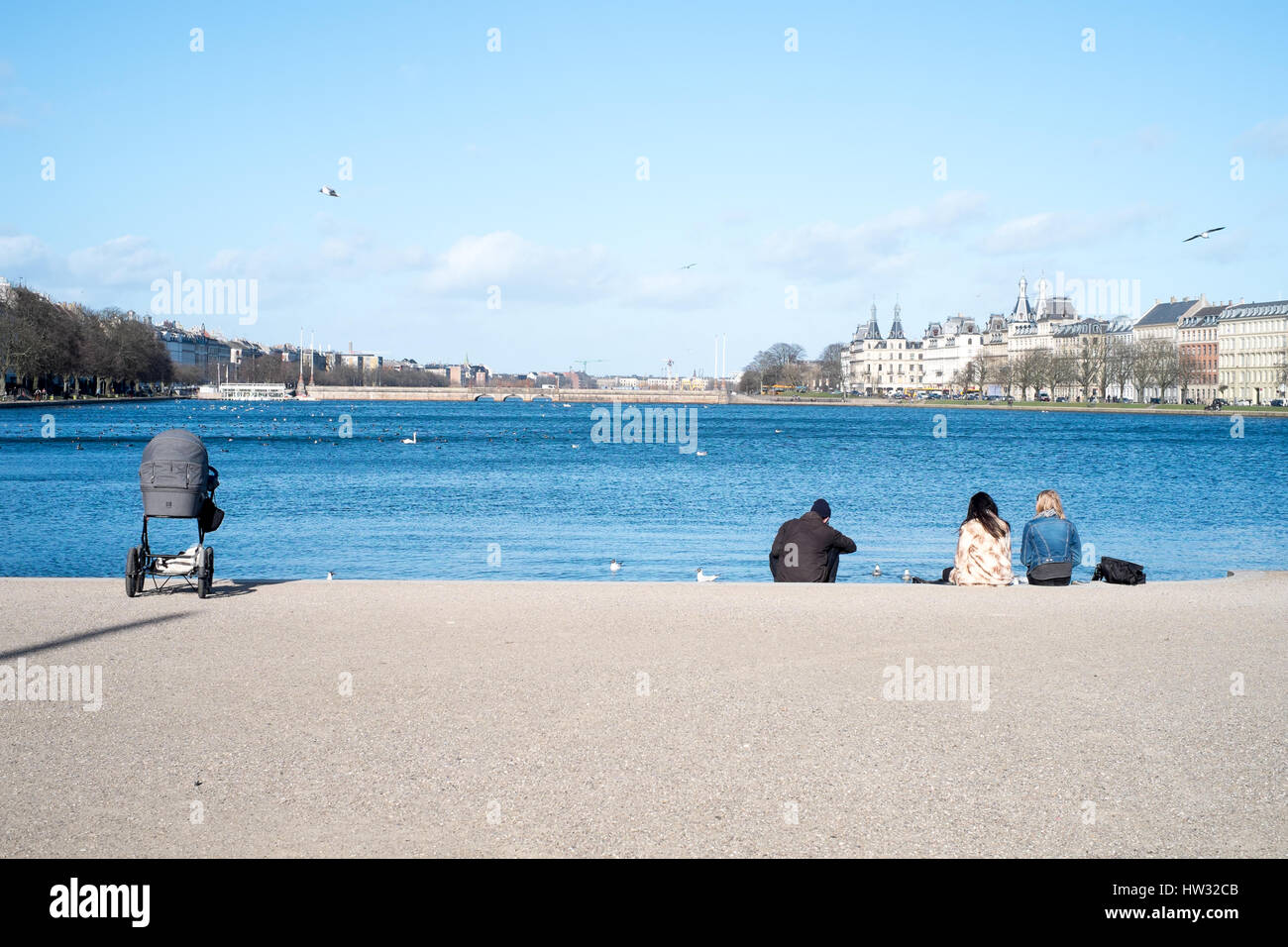 Relaxing locals enjoying an early spring day at Søerne (The Lakes) in early spring, Copenhagen, Denmark - Stock Image