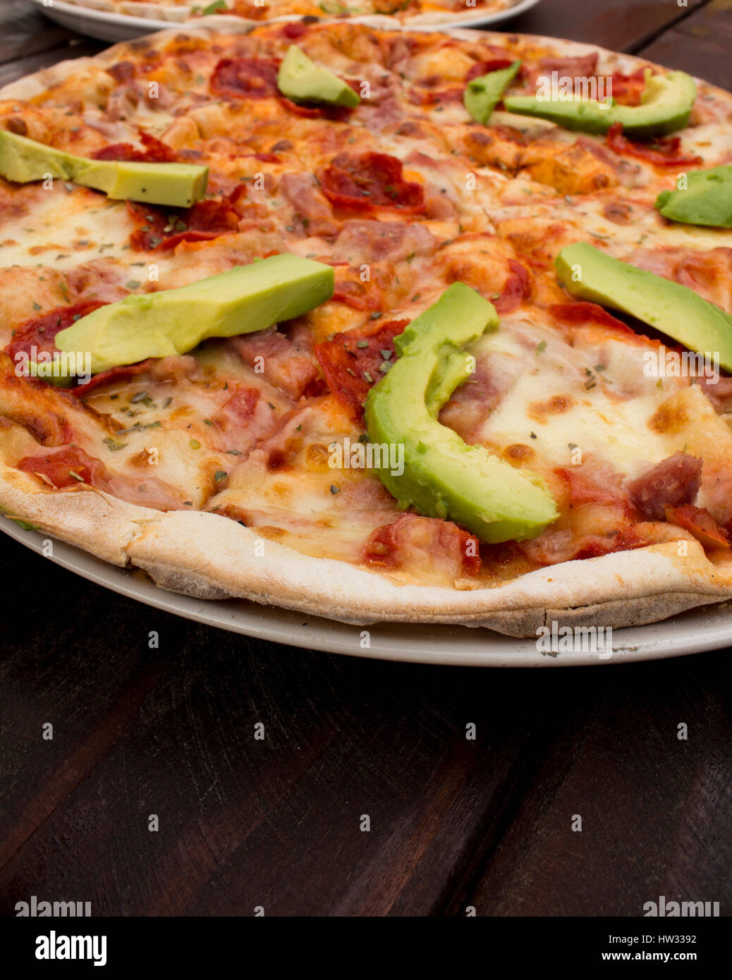 Pizza on dark wooden table top with fresh ingredients - Stock Image