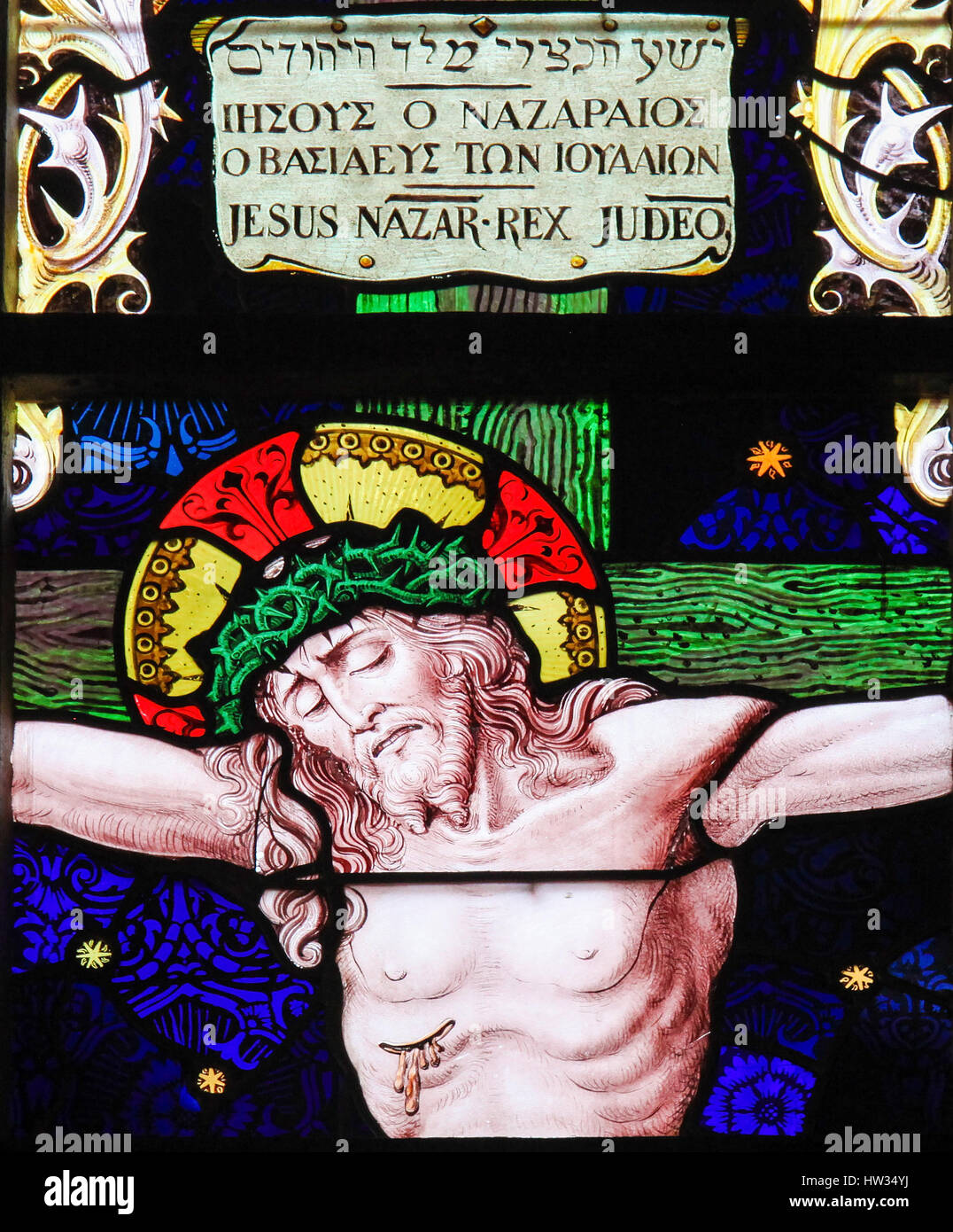 Stained Glass in the Church of Our Blessed Lady of the Sablon in Brussels, Belgium, depicting Jesus on the Cross - Stock Image