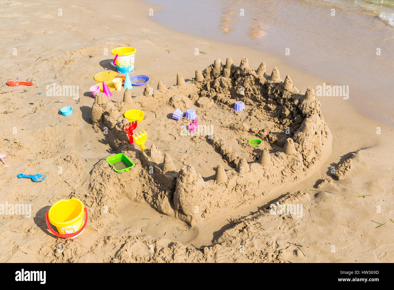 A sand castle with a lot of plastic beach toys with no children in the picture. Stock Photo