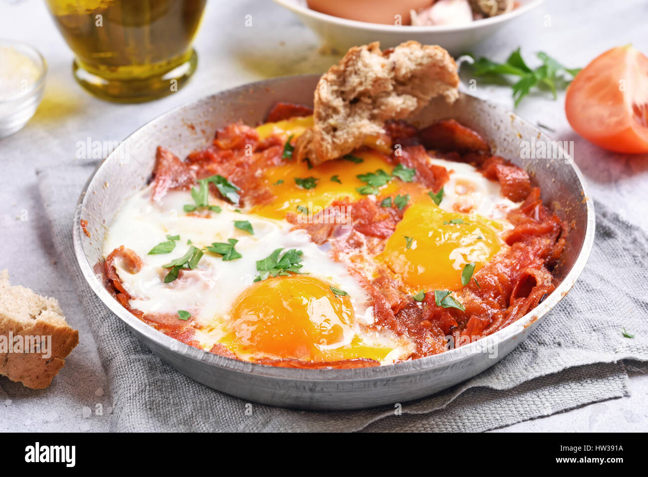 Breakfast with fried eggs and bacon in frying pan, close up view - Stock Image