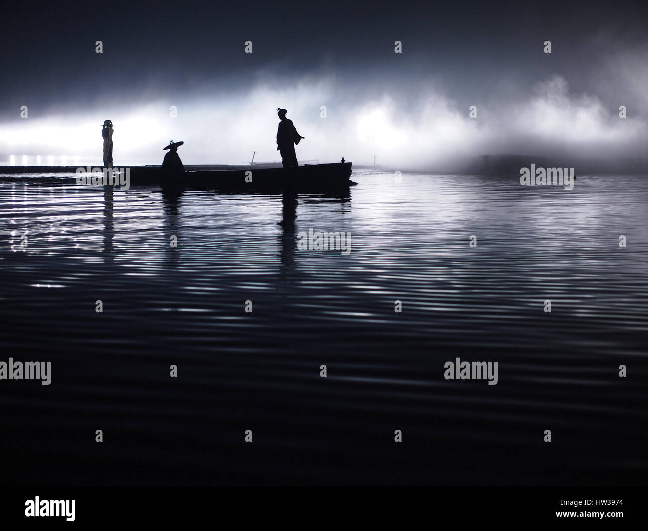 Sunset, twilight - Boat with asian people - Ocean, river landscape - Hanzhong, Shaanxi, China - Stock Image