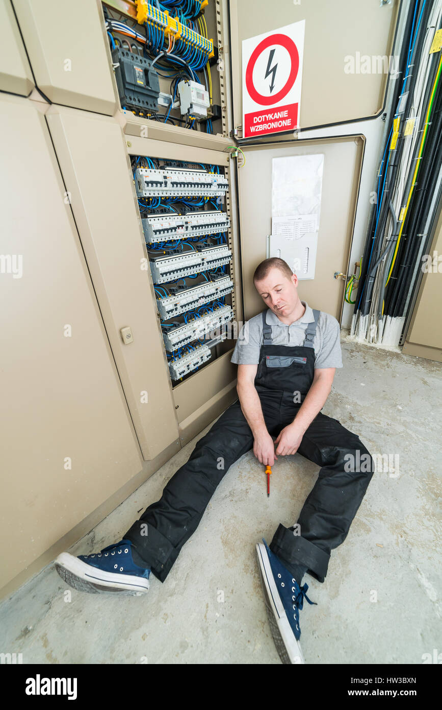 electrician electrocuted lying on the ground - Stock Image