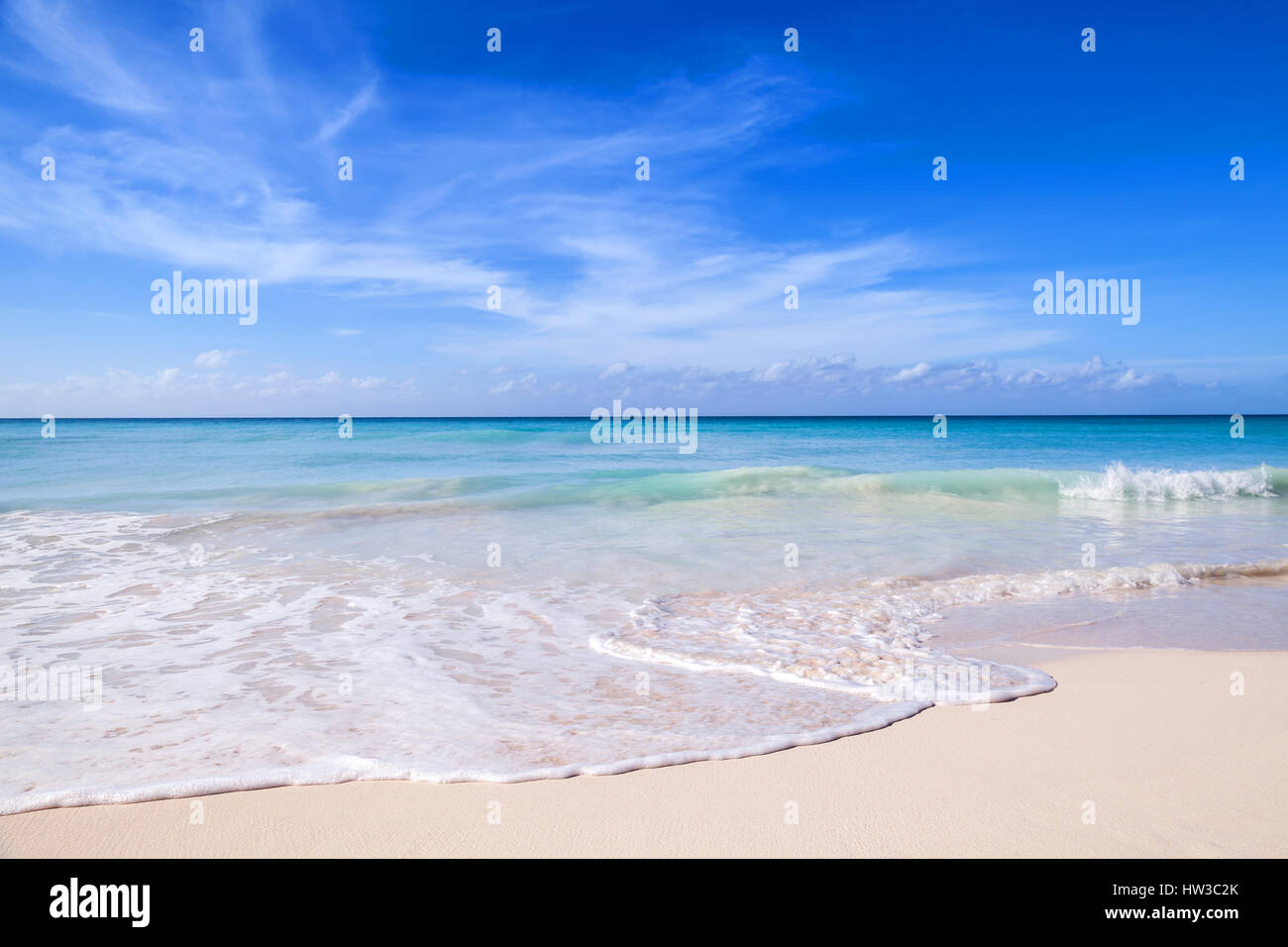 Tropical beach background, white sand, azure shore water under cloudy blue sky. Caribbean Sea coast, Dominican republic, - Stock Image