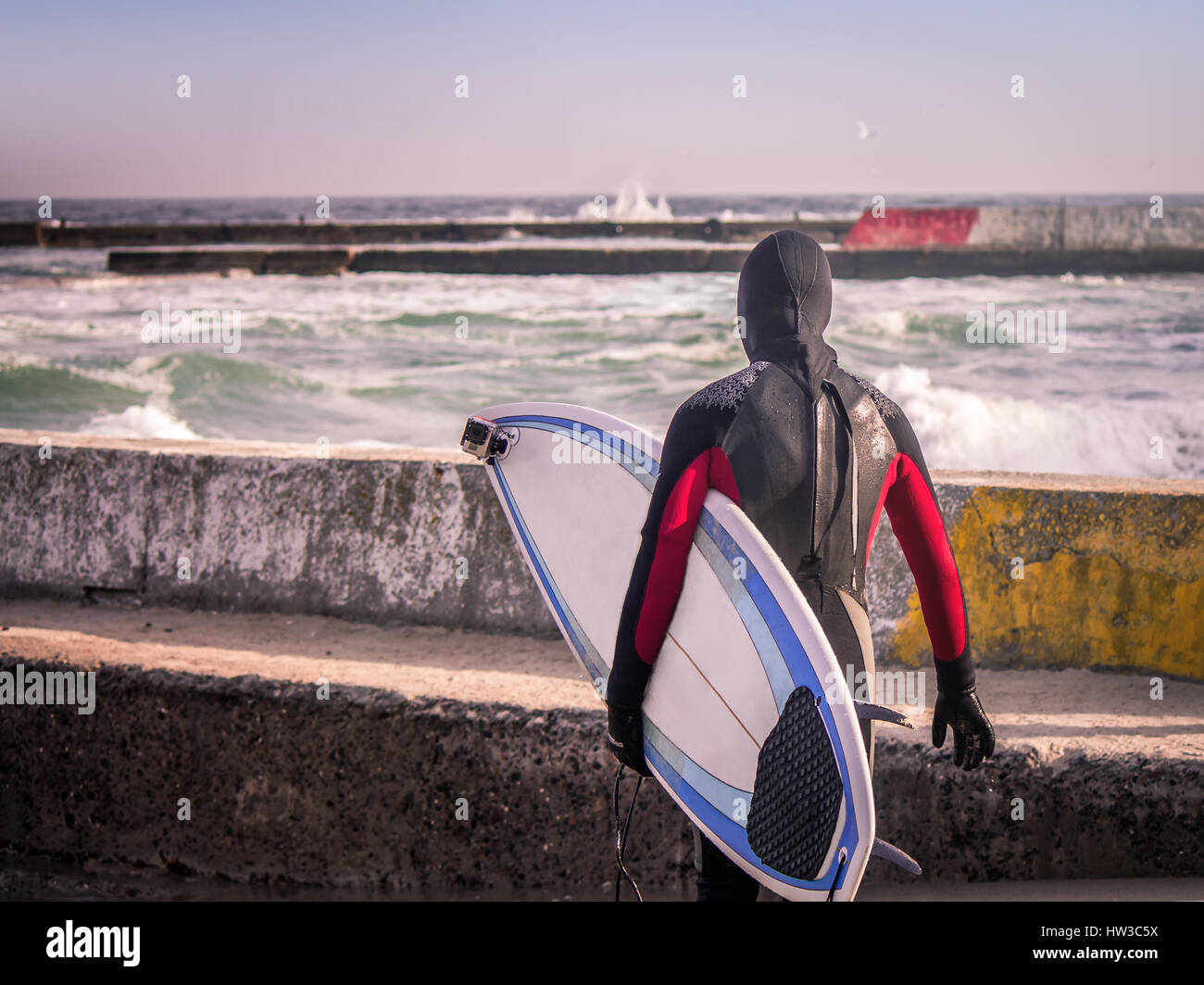 Surfer on the pier walks  into water wearing a wetsuit in winter. Cold surfing. Wave splash. waterproof suit Stock Photo