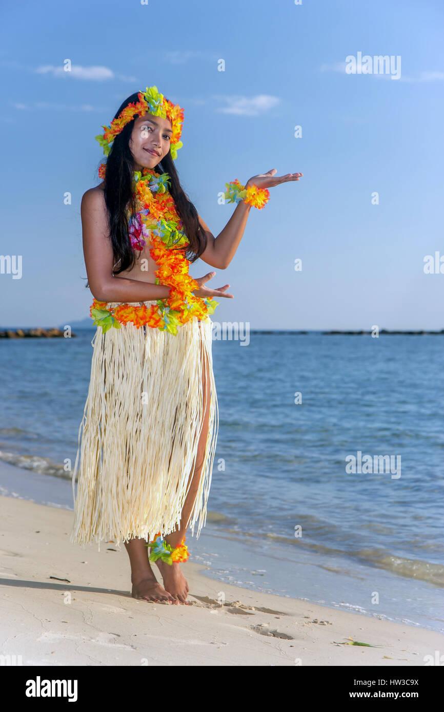 Hula Hawaii dancer dancing on the beach with horizon of sea. Ethnic woman in costume dancer Hawaii hula dancing Stock Photo