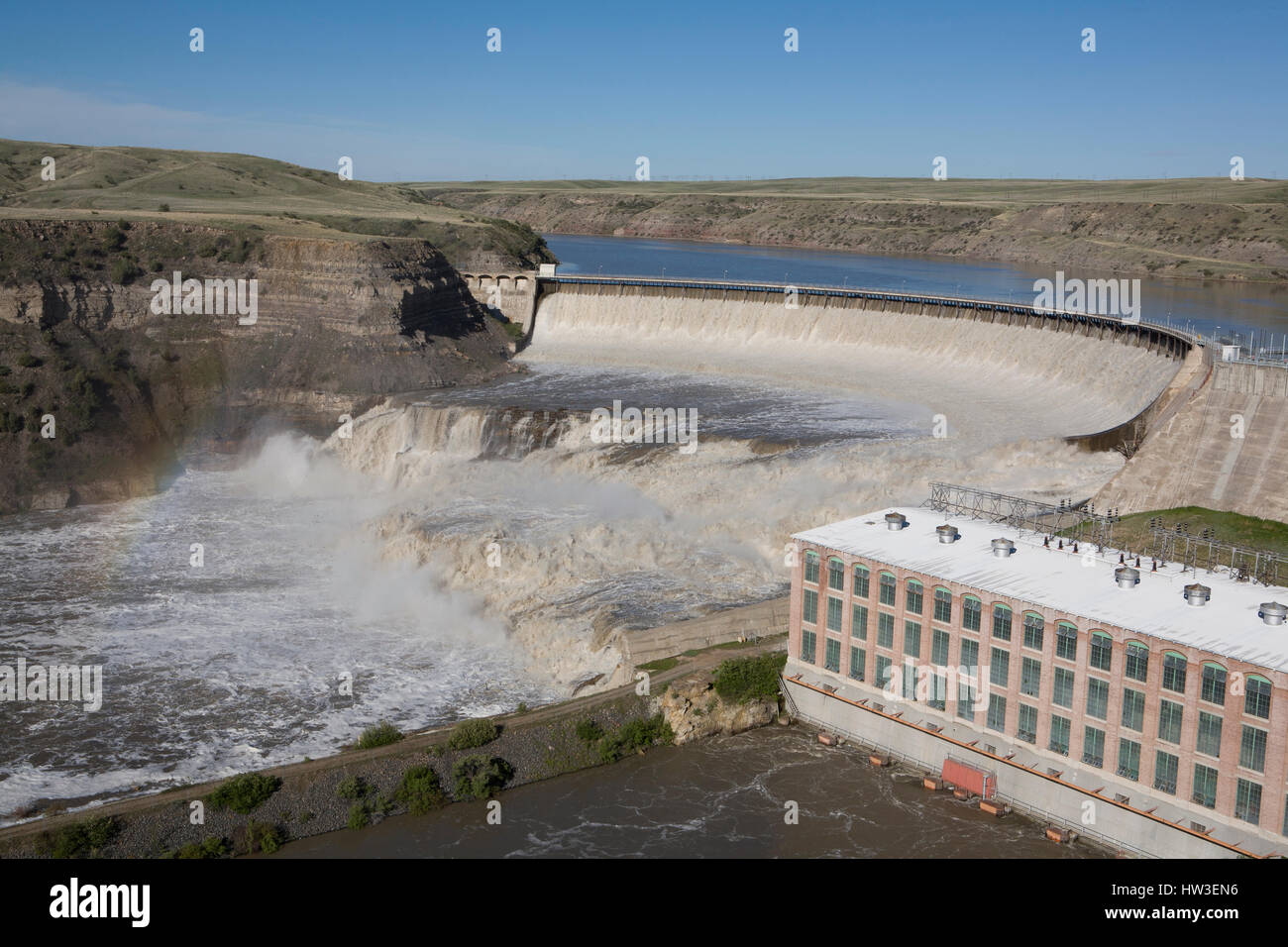 Water pours over Ryan Dam during spring runoff.  The Missouri River is running at approximately 24,000 cfs.  Median - Stock Image