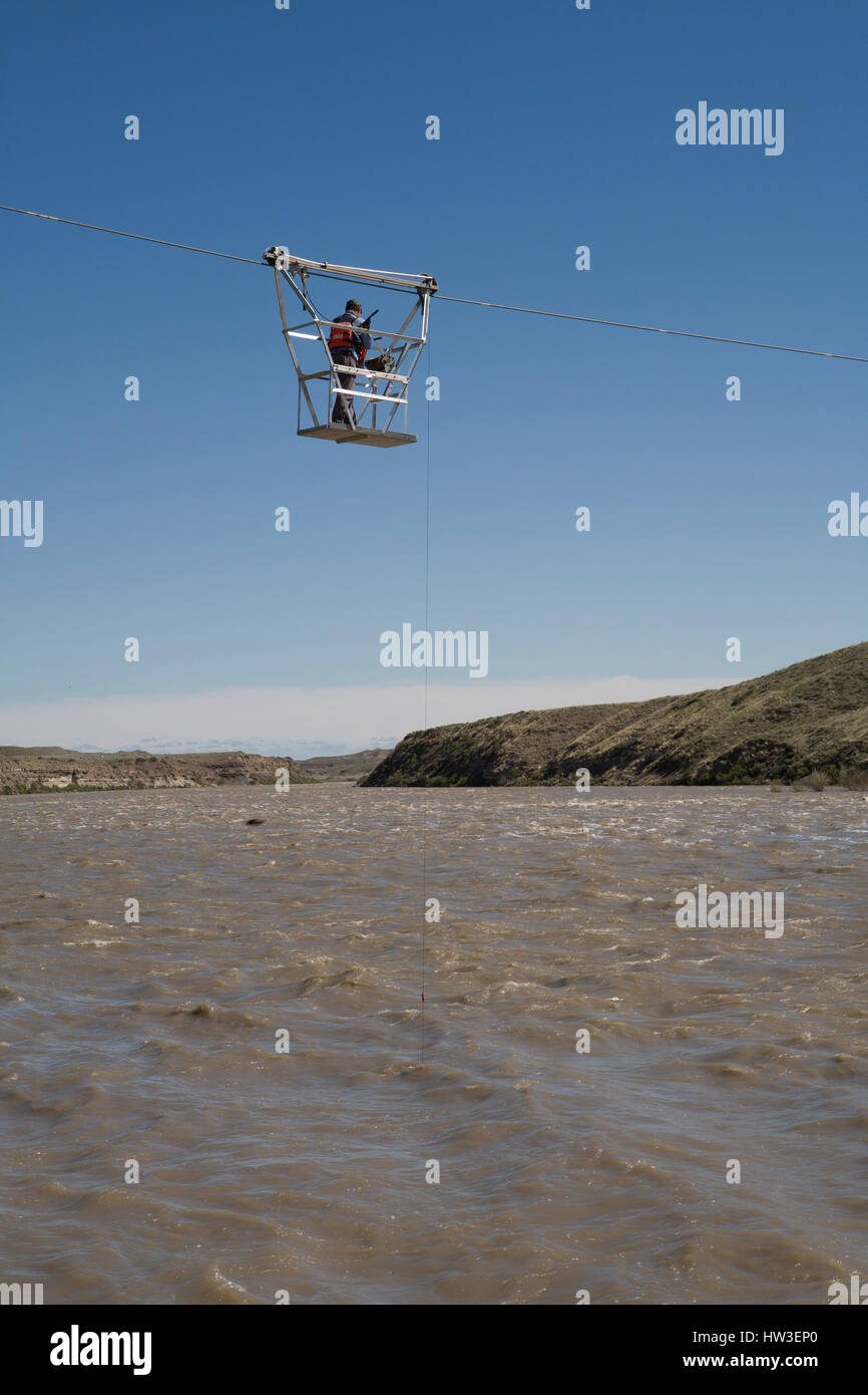 Hydrologic technician measures river flow from basket hanging over the Missouri River. Flow calculation verify station - Stock Image