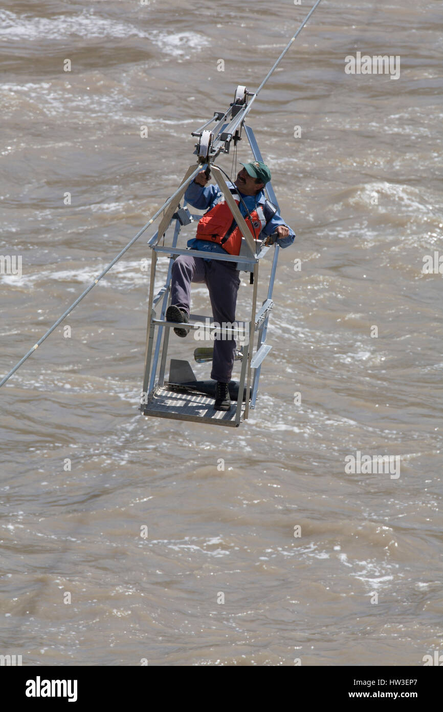 Hydrologic technician muscles his cable basket back to the starting point after taking Missouri River current measurements - Stock Image