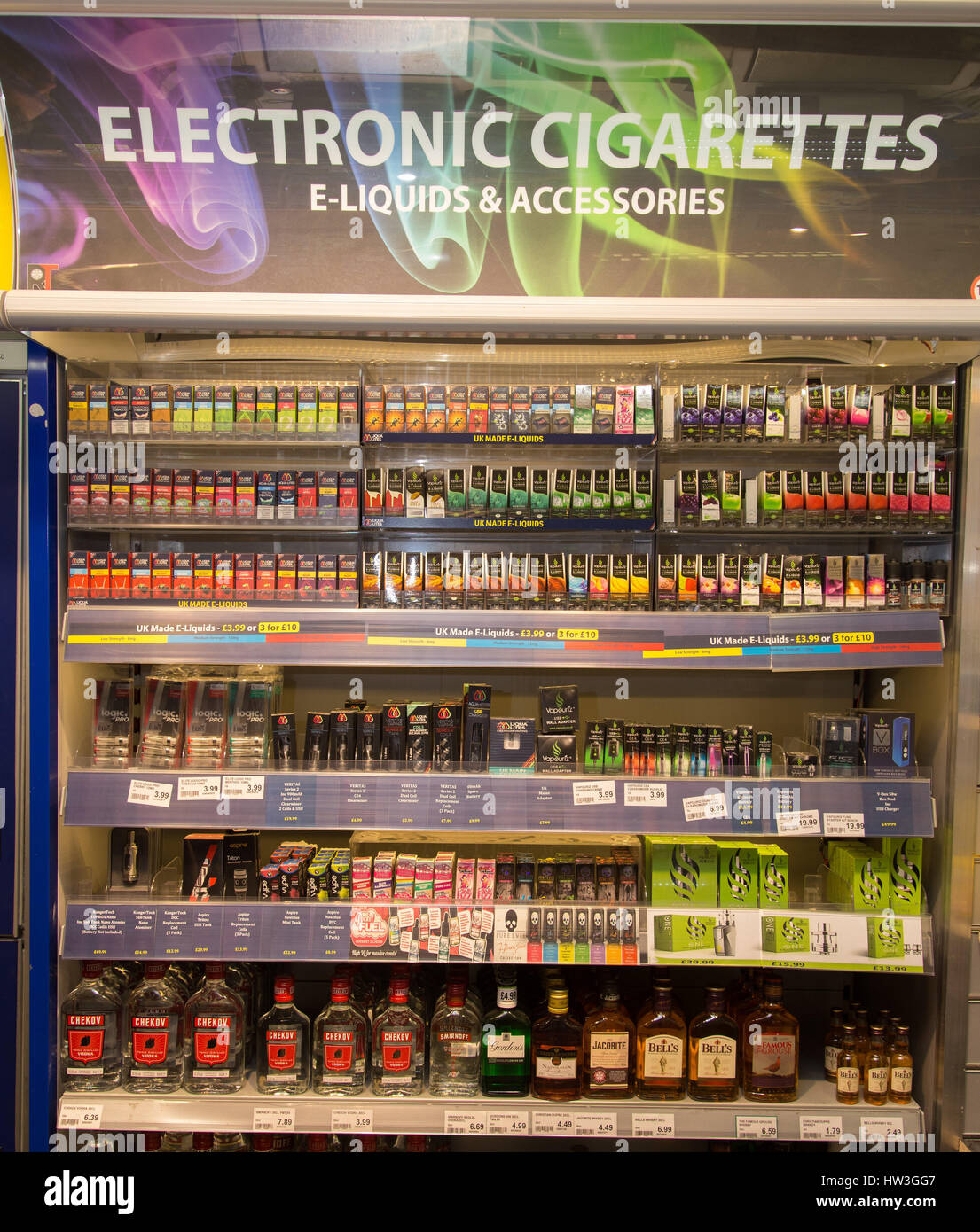 Electronic cigarettes for vaping and spirits vodka, gin, whisky, brandy in a shop display cabinet. - Stock Image