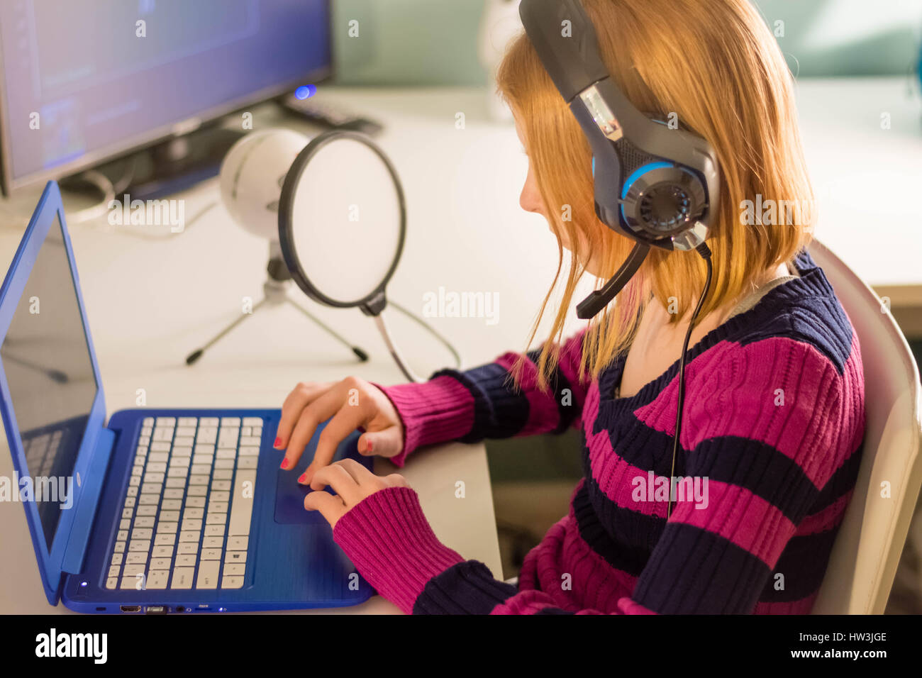 Tween playing on laptop with headphones on and microphone beside her. - Stock Image