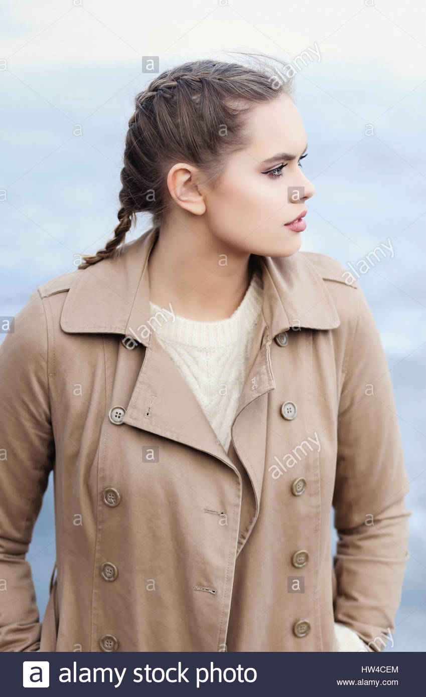 Young woman with braids and a trench coat, looking away - Stock Image