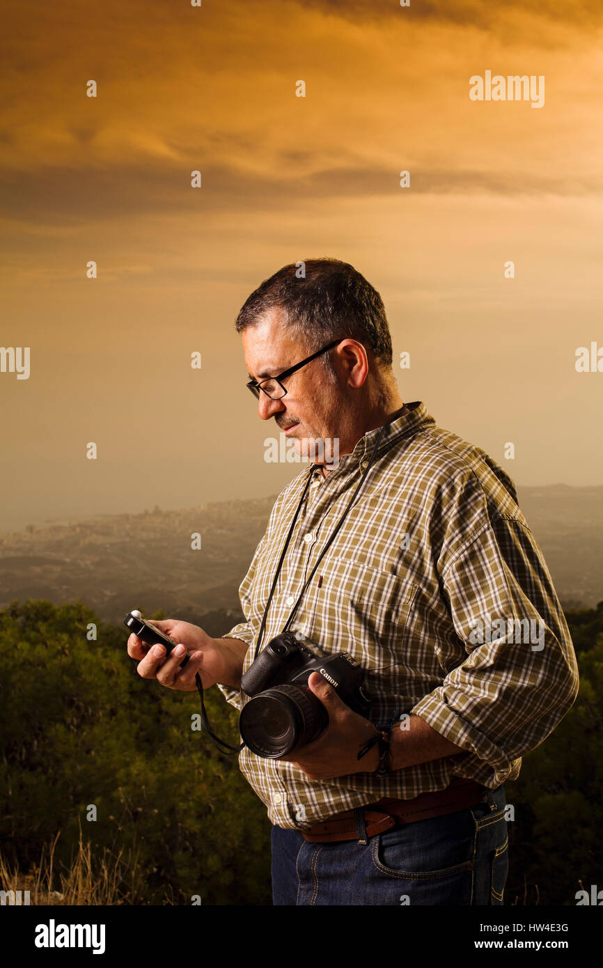 Photographer assistant measuring the light in a photo shoot outdoors at sunset Stock Photo
