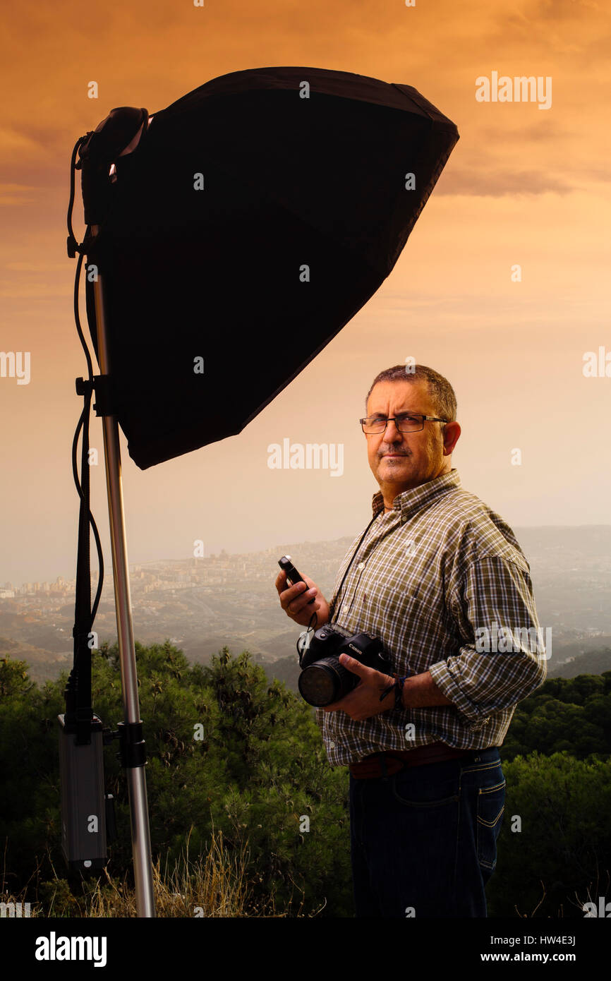 Photographer assistant measuring the light in a photo shoot outdoors at sunset - Stock Image