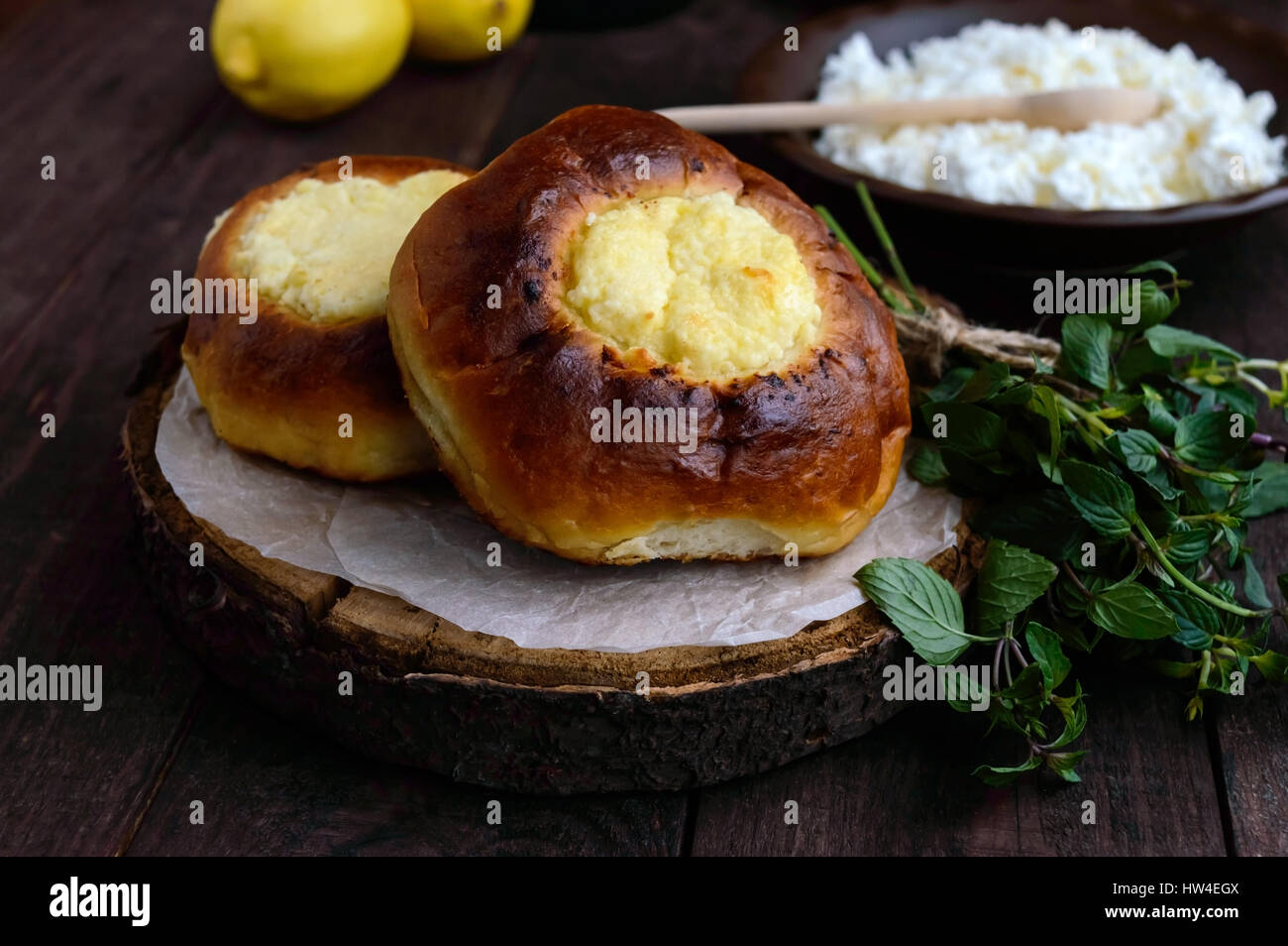 Vanilla cottage cheese buns (cheesecake) on dark wooden background. - Stock Image