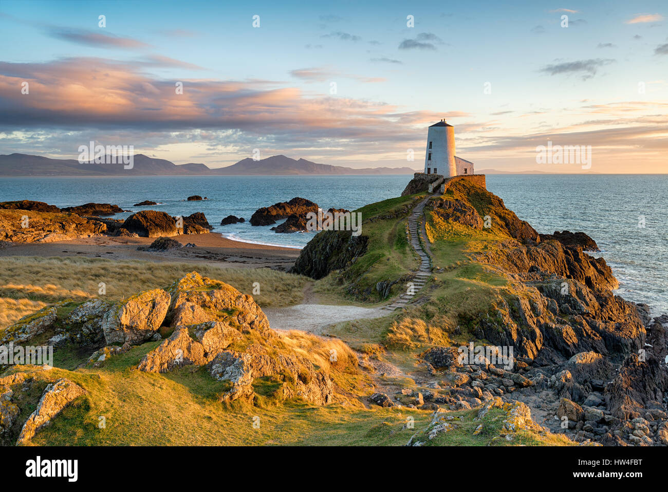 Sunset at Ynys Llanddwyn island on the coast of Anglesey in North Wales with the mountains of Snowdonia in the distance. - Stock Image